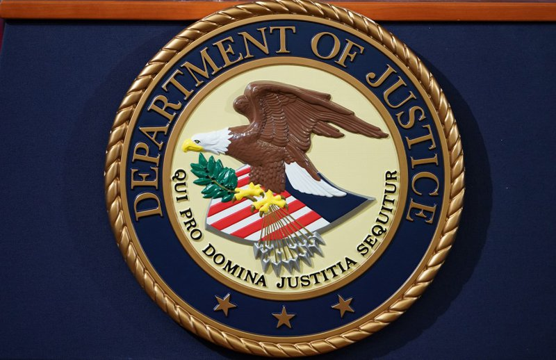 The Department of Justice seal is seen on a lectern ahead of a press conference announcing efforts against computer hacking and extortion at the Department of Justice in Washington, DC on November 28, 2018.