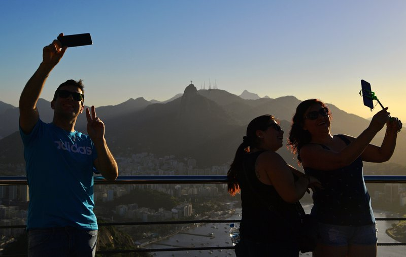 d93c2516acc780 Tourists take selfies at Sugarloaf Hill on June 7, 2019. CARL DE SOUZA /