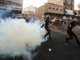 An Iraqi protester returns a tear gas canister thrown by security forces during clashes