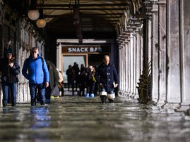 People walk across a floode darcade by St. Mark's Square on November 14, 2019 in Venice.