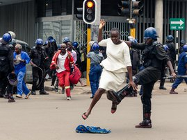 An anti-riot police man in Zimbabwe tackles a woman with his boot as they dispersed a crowd gathered to hear an address by leader of the MDC