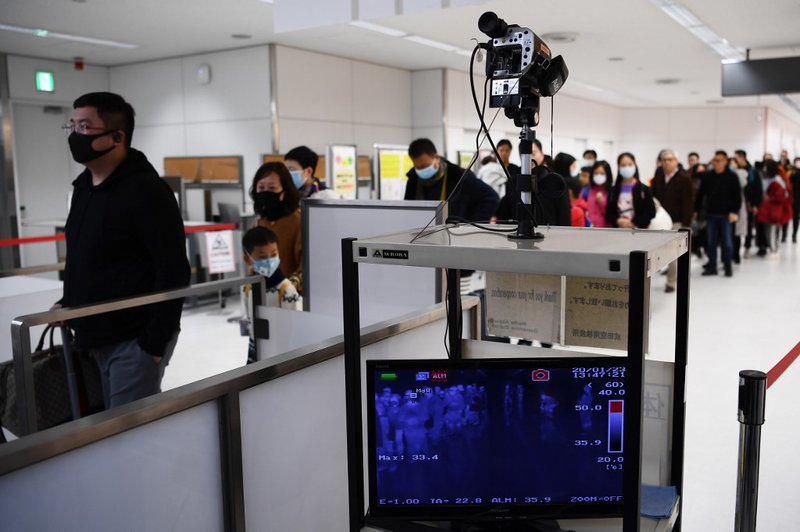 Passengers who arrived on one of the last flights from the Chinese city of Wuhan walk through a health screening station at Narita airport in Chiba prefecture, outside Tokyo, on January 23, 2020, as countries screen for anyone showing symptoms of a SARS-l