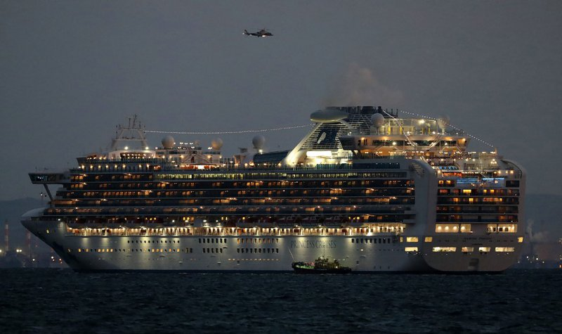 A small boat is pictured next to the Diamond Princess cruise ship with over 3,000 people as it sits anchored in quarantine off the port of Yokohama on February 4, 2020, a day after it arrived with passengers feeling ill. Japan has quarantined the cruise s