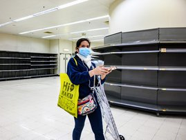 A shopper wearing a protective facemask walks past bare supermarket shelves, usually stocked with toilet paper and kitchen rolls, in Hong Kong on February 6, 2020. Panic buyers in Hong Kong have descended on supermarkets to snap up toilet paper after fals