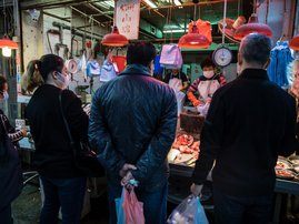 A fish monger wearing a protective face mask prepares an order for a customer at a fresh food market in Hong Kong on February 9, 2020, as a preventative measure after a coronavirus outbreak which began in the Chinese city of Wuhan. The previously unknown