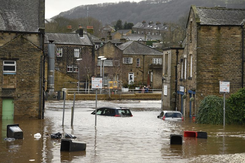 Cars are seen submerged as flood water covers the roads and car parks in Mytholmroyd, northern England, on February 9, 2020, after the River Calder burst its banks as Storm Ciara swept over the country. Britain and Ireland hunkered down Sunday for a power