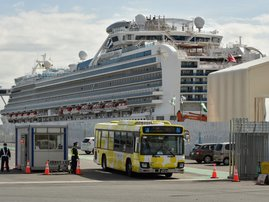 A bus carrying passengers who disembarked from the Diamond Princess cruise ship (back) in quarantine due to fears of the new COVID-19 coronavirus, leaves the Daikoku Pier Cruise Terminal in Yokohama on February 19, 2020. Relieved passengers began leaving