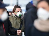 Residents wearing respiratory mask wait to be given access to shop in a supermarket in small groups of forty people on February 23, 2020 in the small Italian town of Casalpusterlengo, under the shadow of a new coronavirus outbreak, as Italy took drastic c