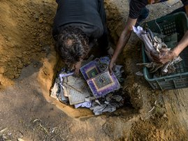People bury copies of the Koran after they recovered from a burnt-out mosque following clashes between people supporting and opposing a contentious amendment to India's citizenship law, in New Delhi on February 26, 2020. Four more people have died in some