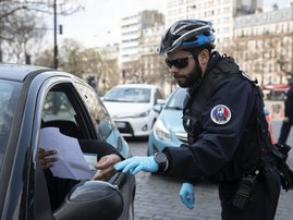 A French police officer checks that motorists are carrying the correct mobility document at the Place d'Italie in Paris, on March on 18, 2020. A strict lockdown requiring most people in France to remain at home came into effect at midday on March 17, 2020