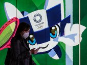 In this file photo taken on March 11, 2020 a woman wearing a face mask walks in the tunnel of a metro station with a poster of Miraitowa, official mascot of the 2020 Summer Olympics in Tokyo. Japan has asked for a one-year postponement of the Tokyo 2020 G
