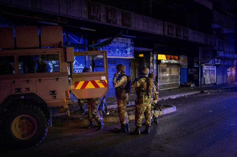 Members of the South African National Defence Force (SANDF) climb on an Armoured Personal Carrier (APC) during an operation in the Johannesburg CBD, on March 27, 2020. South Africa came under a nationwide military-patrolled lockdown on March 27, 2020, joi