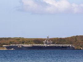 In this file photo the aircraft carrier USS Theodore Roosevelt is docked at Naval Base Guam in Apra Harbor on April 10, 2020. A sailor who was aboard the USS Theodore Roosevelt aircraft carrier died Monday of COVID-19, the first fatality from nearly 600 c