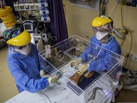 Doctor Jana du Plessis (R) and Doctor Anele Mtanjana (L) demonstrate how to use an intubox for worker safety designed at the Charlotte Maxeke Hospital in Johannesburg, on April 15, 2020. A team of medical professionals from the South African public hospit