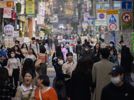 In a photo taken on May 10, 2020, people wearing face masks walk along a street in the Hongdae district of Seoul. South Korea announced its highest number of new coronavirus cases for more than a month on May 11, driven by an infection cluster in a Seoul