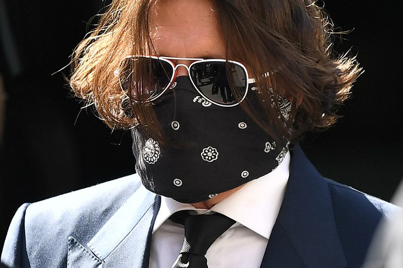 Hollywood actor Johnny Depp (3R), wearing a face mask or covering due to the COVID-19 pandemic, arrives on the first day of his libel trial against News Group Newspapers (NGN), at the High Court in London, on July 7, 2020. A libel trial was due to begin o