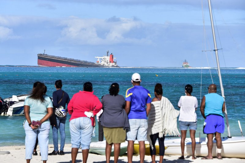 Bystanders look at MV Wakashio bulk carrier that had run aground and from which oil is leaking near Blue Bay Marine Park in south-east Mauritius on August 6, 2020. The carrier, belonging to a Japanese company but Panamanian-flagged, ran aground on July 25