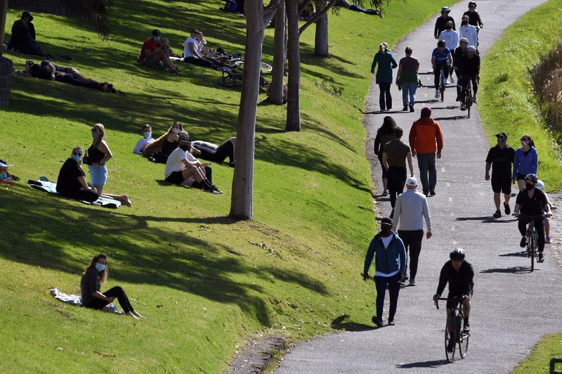 People exercise at a park along the Yarra River in Melbourne on September 27, 2020 as an overnight curfew in Australia's second-biggest city will be lifted from September 28, almost two months after it was imposed to counter a surging COVID-19 coronavirus