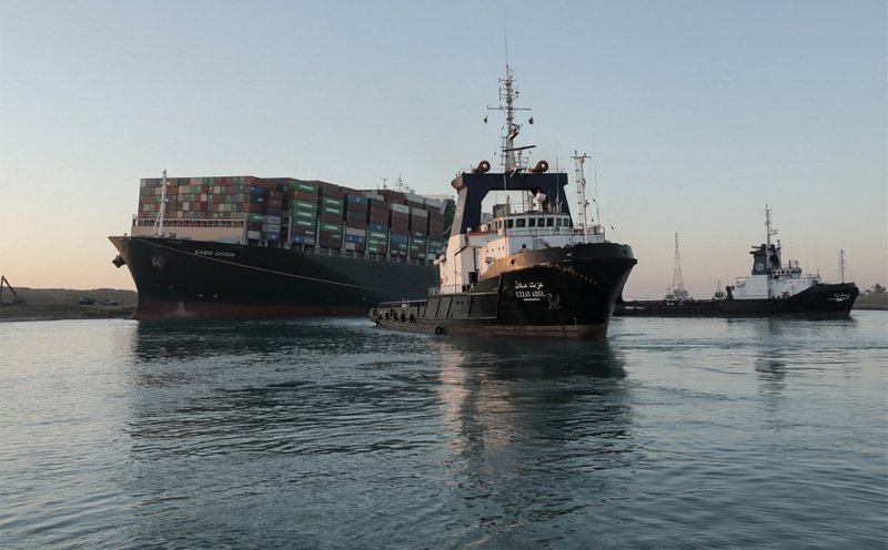 A handout picture released by the Suez Canal Authority on March 29, 2021 shows tugboats pulling the Panama-flagged MV 'Ever Given' (operated by Taiwan-based Evergreen Marine) container ship, a 400-metre- (1,300-foot-)long and 59-metre wide vessel, lodged