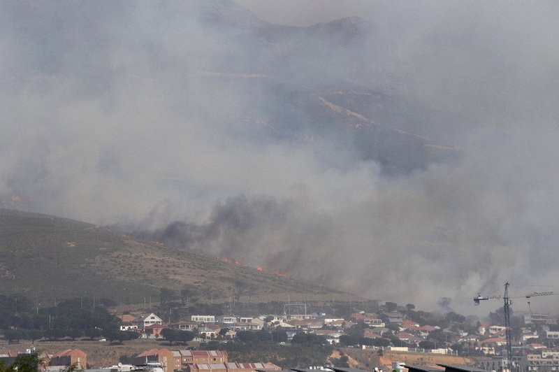 A general view of the forest fire, burning down the mountain towards Philip Kgosana Drive, one of the main arterial roads into the city centre, threatening the suburb of Walmer Estate, in Cape Town on April 19, 2021. The fire, which broke out on April 18,