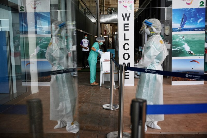 """A medical worker prepares Covid-19 coronavirus swab test for international passengers arriving for the """"Phuket Sandbox"""" tourism scheme that allows vaccinated visitors at Phuket International Airport in Phuket on July 1, 2021."""