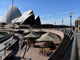 Empty table and chairs are seen at a closed restaurant along a quiet Sydney Opera House forecourt in Sydney on July 6, 2021, as the city remains in lockdown for a second week to contain an outbreak of the highly contagious Delta Covid-19 variant. AFP