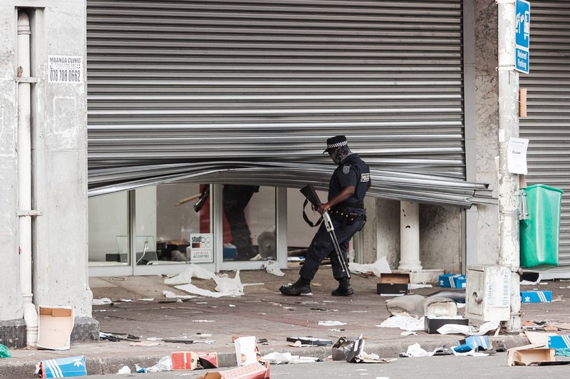 A member of the Durban Metro Police looks at a looted retail store in central Durban, on July 11, 2021. Several shops are damaged and cars burnt in Durban, following a night of violence. Police are on the scene trying to control further protests. It is un