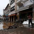 A resident cleans the pavements of a street following heavy rains and floods in Bad Neuenahr-Ahrweiler, western Germany, on July 15, 2021. German authorities said late July 15, 2021 that at least 58 people had likely died in massive storms and flooding in