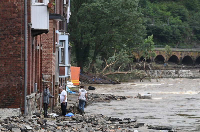 Local residents stand near damaged and flooded road in Trooz, near Liege, on July 16, 2021. The situation remains critical as the water keep rising after the heavy rainfall of the previous days. The death toll from devastating floods in Europe soared to a