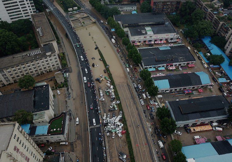 An aerial view shows cars sitting in floodwaters at the entrance of a tunnel after heavy rains hit the city of Zhengzhou in China's central Henan province on July 22, 2021.