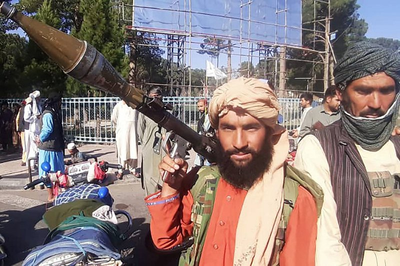 In this picture taken on August 13, 2021, a Taliban fighter holds a rocket-propelled grenade (RPG) along the roadside in Herat, Afghanistan's third biggest city, after government forces pulled out the day before following weeks of being under siege.