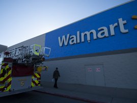 A fire truck sits outside as shoppers continue to enter the store after a shooting in a Walmart