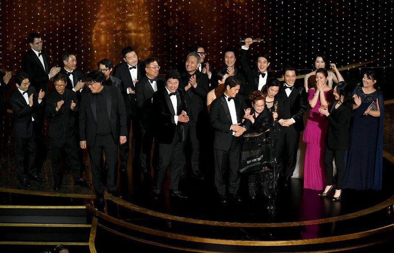 'Parasite' cast and crew such as Cho Yeo-jeong, Park So-dam, Choi Woo-shik, Kang-Ho Song,Yang Jin-mo, Jin Won Han, Kwak Sin-ae, Ha-jun Lee, Yang-kwon Moon, Kang-ho Song, Yeo-jeong Jo, Bong Joon-ho, and Sun-kyun Lee accept the Best Picture award onstage d