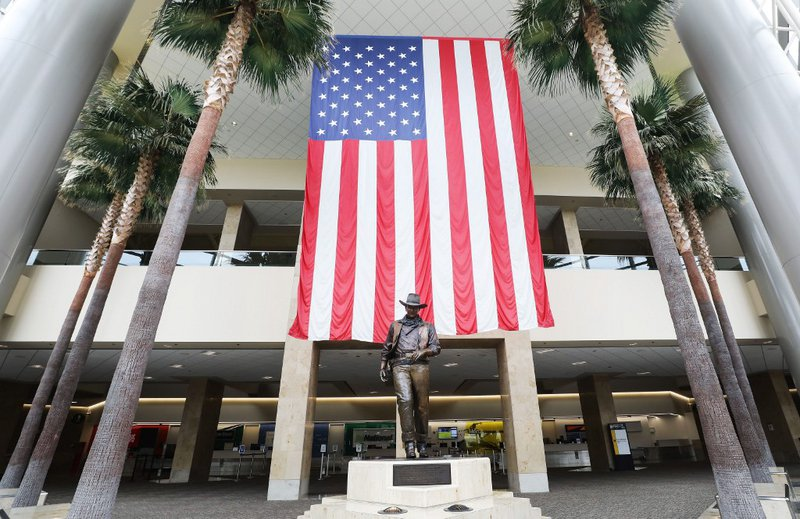 A statue of John Wayne is on display beneath an American flag in John Wayne Airport, located in Orange County, on June 28, 2020 in Santa Ana, California. Orange County Democrats are calling for the name of the airport to be changed and the statue to be r