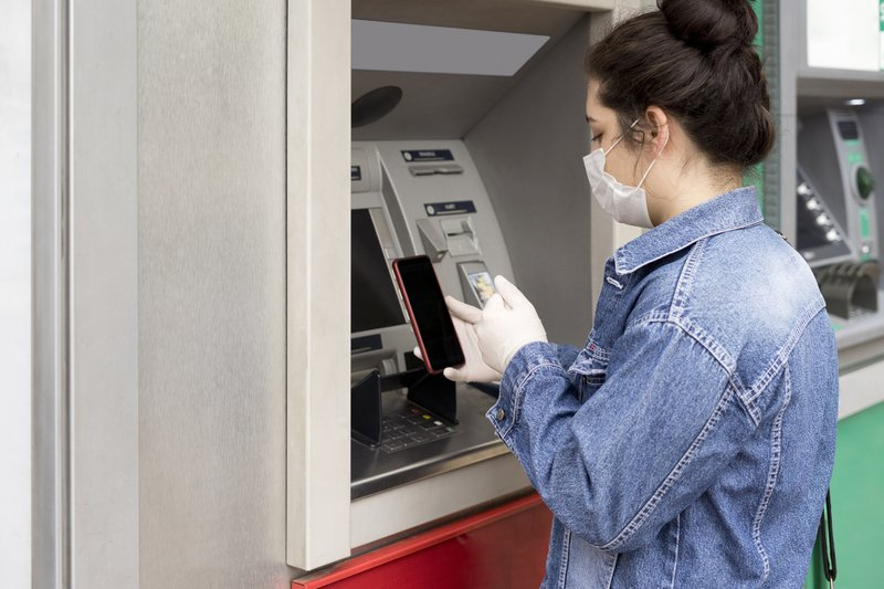 Woman at an ATM/ iStock