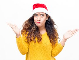 Puzzled woman wearing santa hat