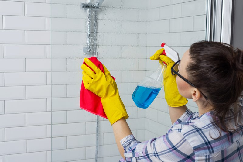 A woman cleaning the shower