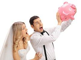 Newlywed couple shaking an empty piggybank