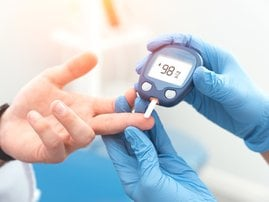 Doctor checking blood sugar level with glucometer