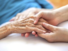 Holding the hand of someone elderly