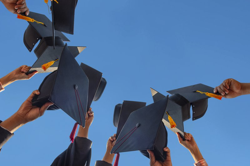 Students holding a shot of graduation cap by their hand