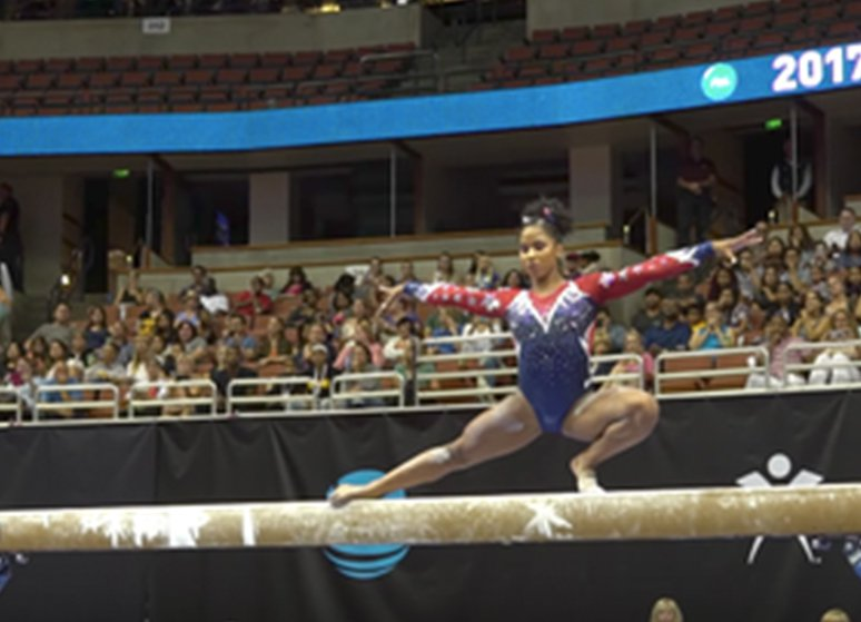 Gymnast almost falls off beam