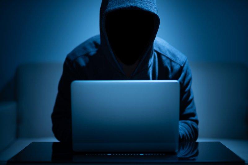 Hacker dark face using laptop