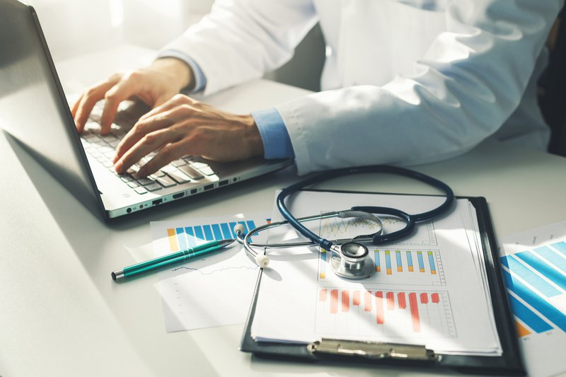 Doctor working with medical statistics and financial reports in office