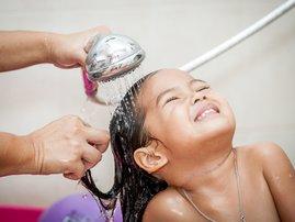 Mother washing baby hair