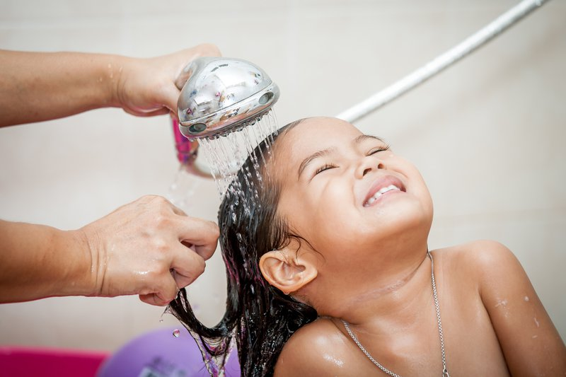 Mother washing baby hair