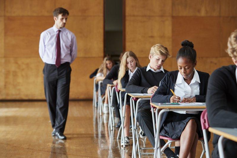 Teenage Students Sitting Examination With Teacher