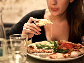 woman holds sliced pizza pexels