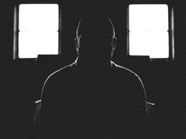 person sitting in a dark room pexels