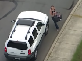 Woman with baby in hand attempts to hijack car!